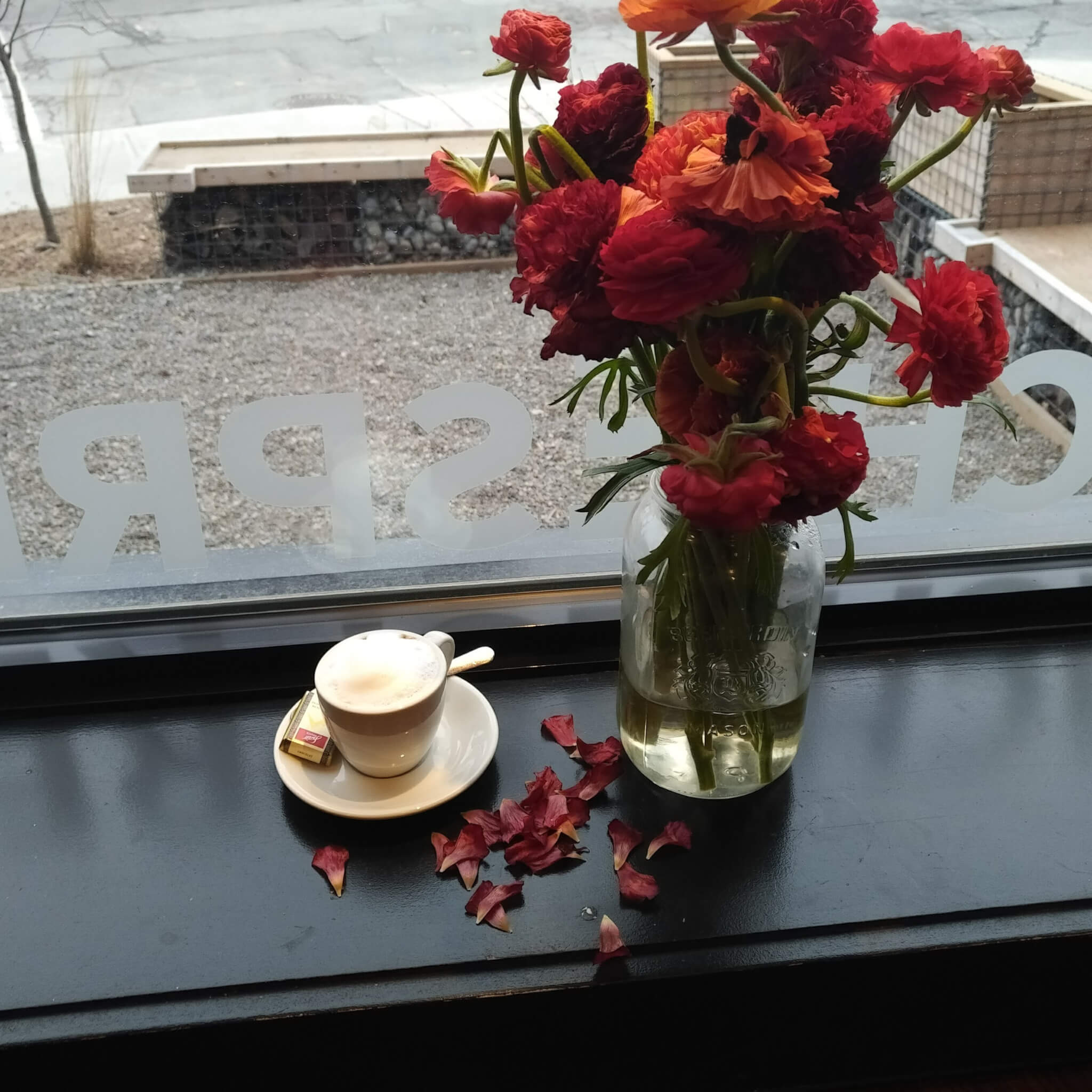 a single macchiato in a white ceramic espresso cup and saucer. A bouquet of red flowers is beside and spilling petals onto the windowsill.